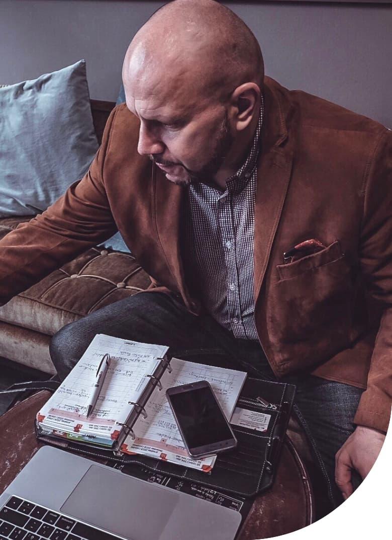 Roman Machník, realitní makléř, sedí u stolu