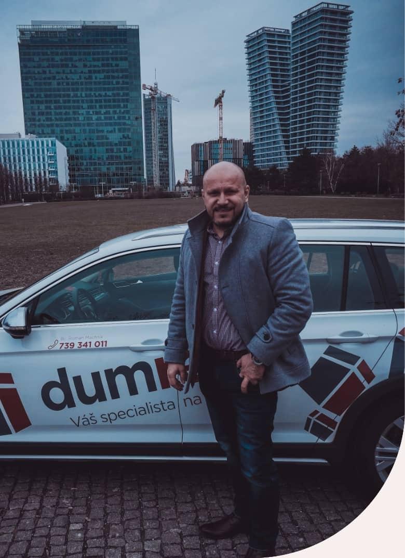 Roman Machník, realitní makléř, stojící u auta